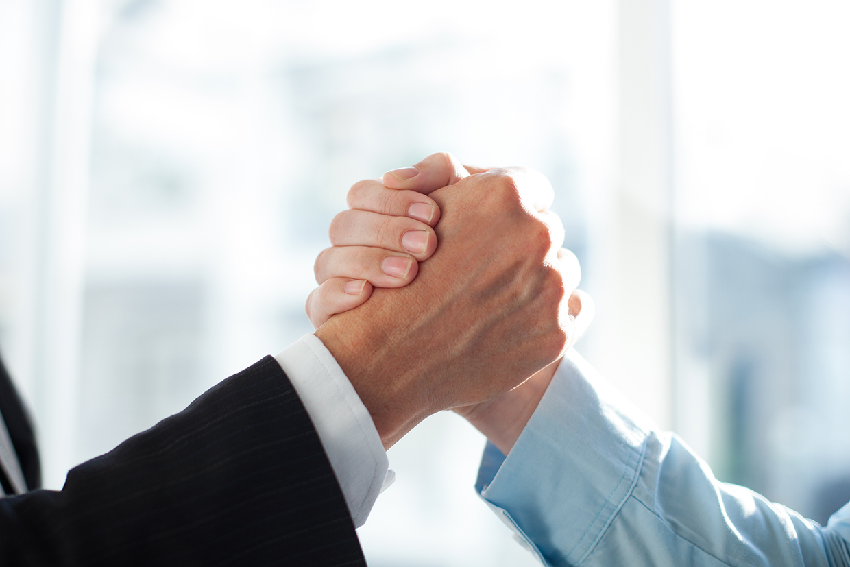 Close-up of two clasped hands of businessmen as sign of strong partnership or team. Unrecognizable men in arm wrestling gesture. Business union concept